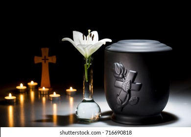 black cemetery urn with white lilly flower in vase