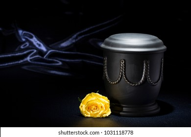 black cemetery urn with yellow rose on dark blue background