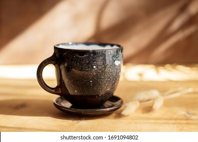 Black ceramic cup on wooden table