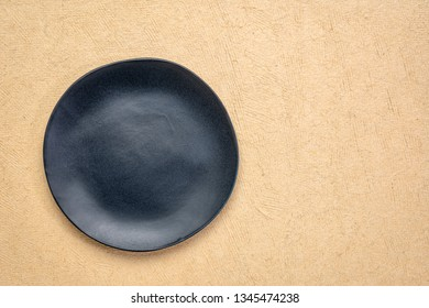 black ceramic plate with an irregular edge on a natural light brown handmade Huun Mayan  paper  with a copy space
