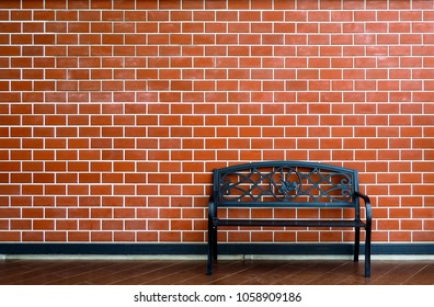 Black chair on brick walls background.