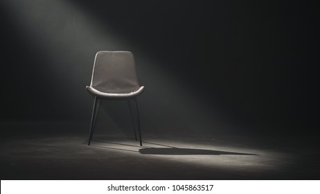A black chair on dark background, low key and wide shot.