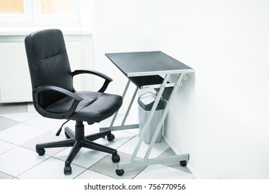 Black chair, table and trash, located in white office space. Minimalistic room.