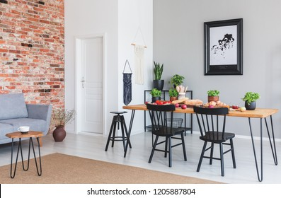 Black chairs at dining table and poster in flat interior with grey sofa against red brick wall. Real photo