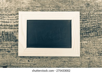 Black chalk board in a light wooden frame on the old wooden table. Toned.