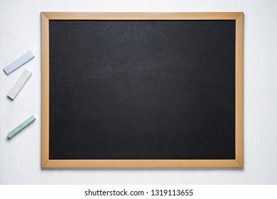 black chalk board and several colored chalk on a white wooden background