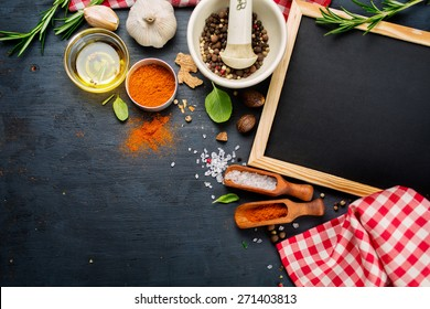 Black chalk board and spices on a dark background, Top view