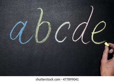 Black chalkboard with latin alphabet hand drawn by chalks. Hand holding chalk