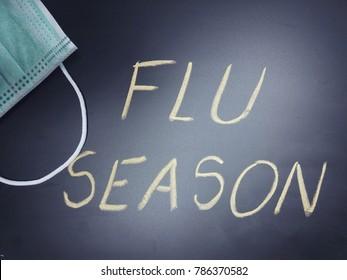 Black chalkboard with phrase Flu season written on it and a face mask, flu season or influenza concept
