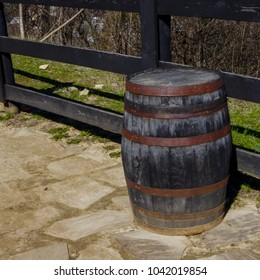 Black charred wooden bourbon barrel with rusty metal bands sitting beside wooden fence
