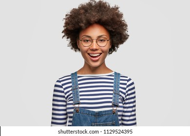 Black cheerful curly African American female happy to finish successful project, dressed in casual striped sweater and denim overalls, smiles positively at camera, isolated over white background