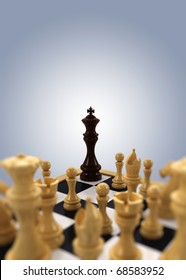 A black chess king is pushed into the corner by all white chess pieces