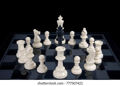 A black chess king surrounded by white pieces
