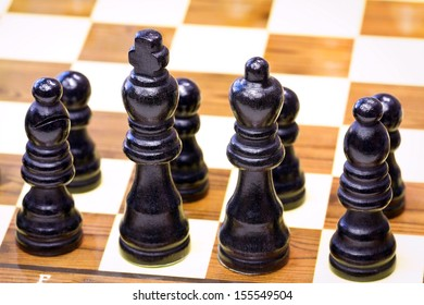Black chess pieces lined up on the first rank