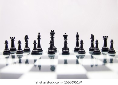 black chess pieces on a glossy chessboard on a white background