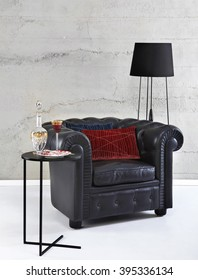 Black chesterfield arm chair and floor lamp on stone wall background, still life