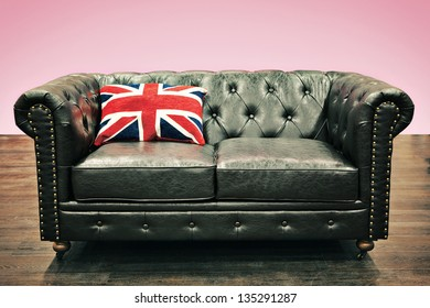 Black Chesterfield couch with union jack cushion in empty room with wooden floor and pink background. More similar furniture in my portfolio