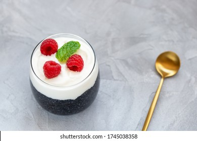 Black chia seed pudding with almond milk, yogurt, activated charcoal powder, raspberries dessert in a glass, spoon. Superfood, vegan food, detox concept. Gray background. Copy space, selective focus