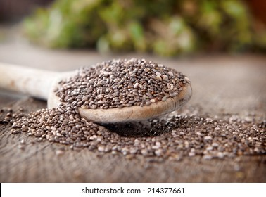 Black chia seeds on a wooden spoon