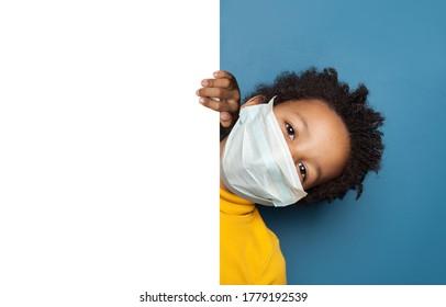 Niño negro con mascara de cara protectora médica sosteniendo un soltero de papel blanco vacío
