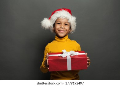 Black child Santa holding red Christmas box with white silky ribbon on gray background
