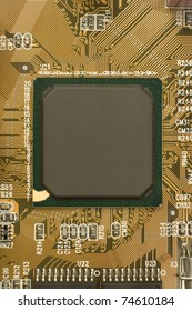 black chip processor with green frame surrounded by brown orange circuit board - motherboard