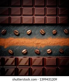 Black chocolate bar, coffee beans, cocoa powder on black slate plate