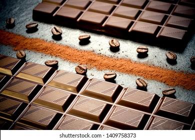 Black chocolate bar, coffee beans, cocoa powder, top view