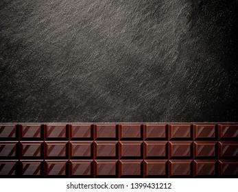 Black chocolate bar on black slate plate, top view