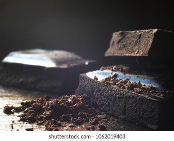Black chocolate close-up, macro photo. Pieces of dark chocolate on a wooden background.