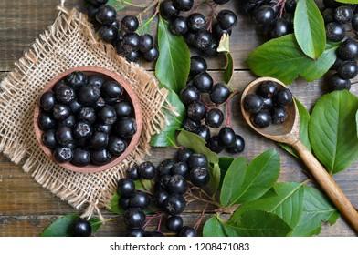 Black chokeberry (Aronia melanocarpa) in wooden bowl, fresh black chokeberry  in wooden spoon and green leaves, top view