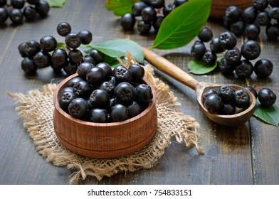 Black chokeberry (Aronia melanocarpa) in wooden bowl, fresh black chokeberry  in wooden spoon.