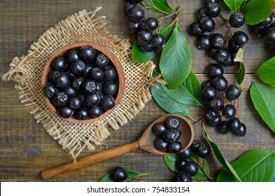 Black chokeberry (Aronia melanocarpa) in wooden bowl, fresh black chokeberry  in wooden spoon and green leaves, top view.