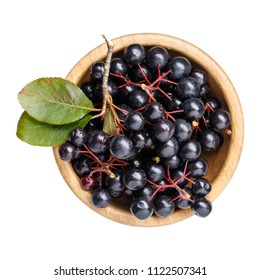 Black chokeberry berries ( Aronia melanocarpa ) in wooden bowl isolated on white. Top view.