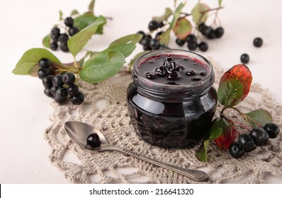 Black chokeberry jam in a small glass jar