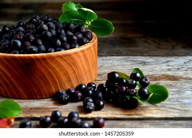 Black chokeberry in wooden utensils on old wooden boards.