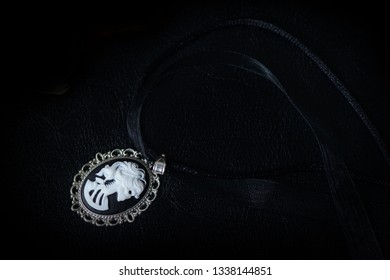Black choker with skeleton cameo pendant on a dark background close up