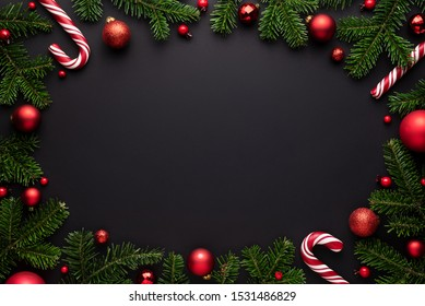 Black Christmas background. Decorative oval frame of fir branches, Christmas balls and Candy canes. Copy space for text