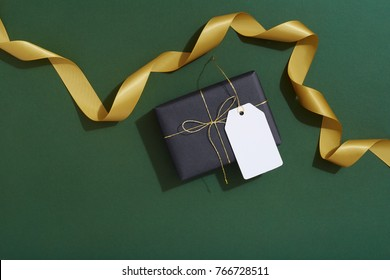 Black Christmas present gift tag on dark green flat lay background with gold ribbon, for men, for him