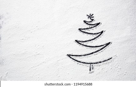 Black Christmas tree on snowy flour background. Top view.