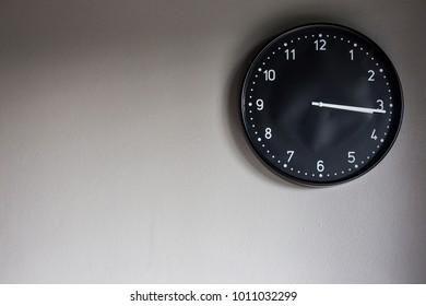 Black circle hanging wall hanging on gray wall. Needle clockwise at 3 digits long at 16 minutes.
