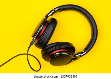 black circum-aural headphones audio for listen music isolated on yellow background