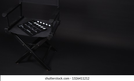 Black Clapperboard or clap board or movie slate with director chair use in video production ,film, cinema industry on black background.