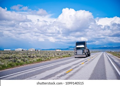 Black classic long haul big rig semi truck transporting commercial cargo covered with tarp on flat bed semi trailer in the flat straight road in Nevada going over horizon with mountain and clouds