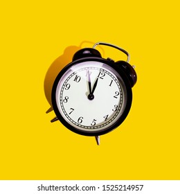 Black classic style alarm clock with hard shadow isolated on yellow background. New Year and start up concept