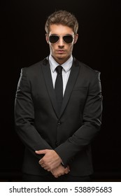Black classic. Vertical portrait of a handsome sexy young man in a suit and dark shades posing confidently on black background