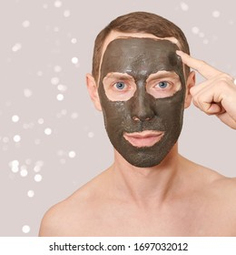 Black Clay Mask on Guy Face. Cosmetology man portrait with mud healthy scrub. Coal nature eco masque. Dermatology mud. Home skin care routine. Skincare male treatment. Applying pure ecology product