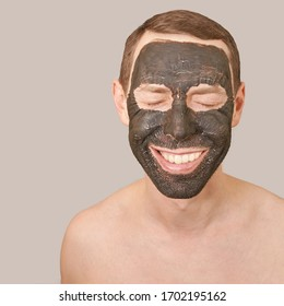 Black Clay Mask on Guy Face. Cosmetology man portrait with mud healthy scrub. Coal nature eco masque. Dermatology mud. Home skin care routine. Skincare male treatment. Pure ecology crack product.