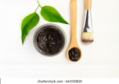 Black clay mineral facial mask in jar with spoon and cosmetic brush, above view white wooden background