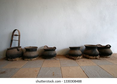 Black clay pots for cooking, placed on the ground with a white cement wall background